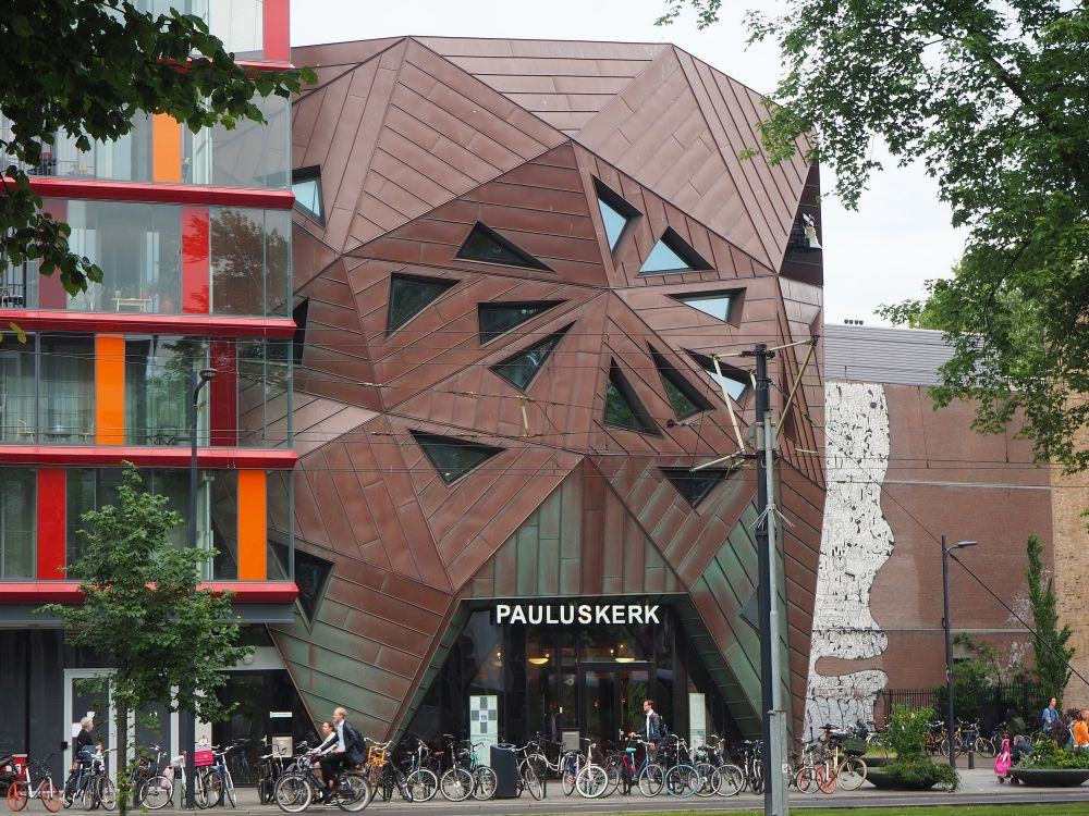Pauluskerk is rusty-red colored and the facade is made of a series of triangular panels fitted together so that it is not a flat front. Rather it bulges over the street.