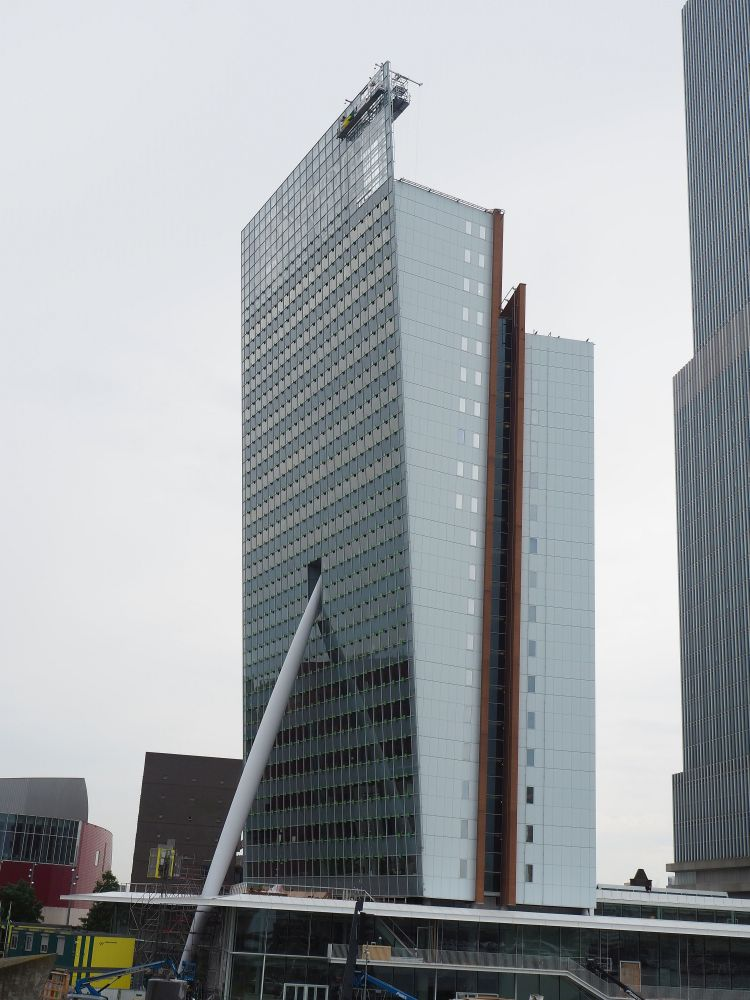 The building looks like a regular glass-sided skyscraper, except that one of the long sides leans out. A huge beam extends from the ground up to the middle of the leaning facade, where it seems to fit into a hole. It makes it look like it's holding up the building.