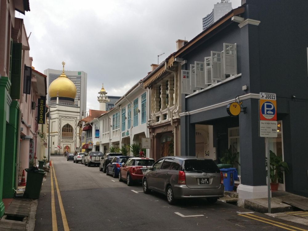 A street in the Kampong Glam neighborhood, with typical older buildings and a covered sidewalk. In the background, the Sultan Mosque.