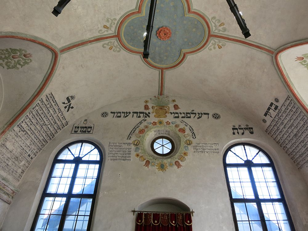The wall straight ahead is arched at the top and extends about two stories high. In the middle, above the ark is a round window, with decorative symbols painted around it as well as words in Hebrew. On the curving left and right walls are more texts in Hebrew. On either side of the ark is a tall arched window.