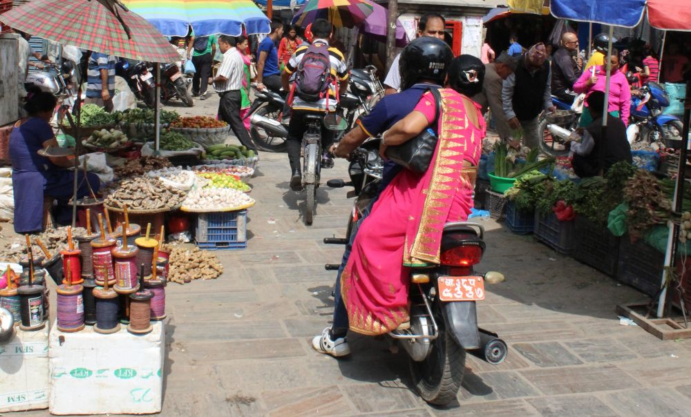 A motorcycle navigating a busy street in Kathmandu, Nepal. A woman sits behind the driver, sidesaddle, holding a bag in one hand and holding on to the driver with the other. The street is crowded with food and vegetable stalls. Travel risks not worth taking.