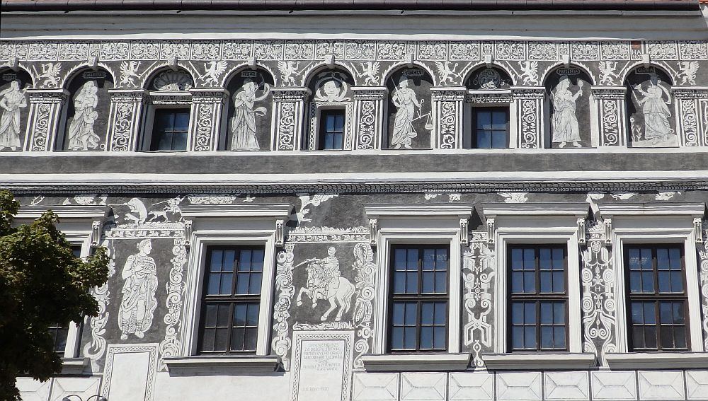 The building is grey and white, with the figures in white on grey backgrounds. The photo shows the 1st and 2nd stories above the ground floor. Between all of the windows are human figures: they look like classical Greek or Romans, wearing togas, holding various items. The only one I recognize off-hand is a figure of justice holding a scale. One of the figures on the lower story looks like a knight on a horse. Trebic, Czech Republic.