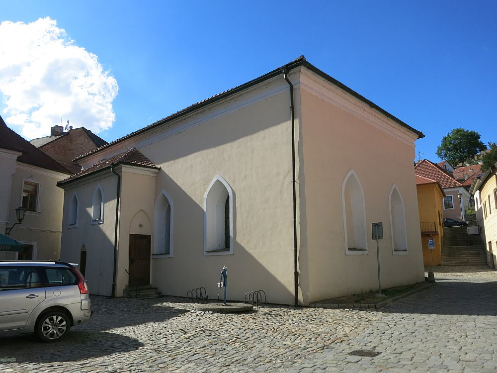 The building is very small and simple, just one story, with quite small windows with pointed tops. The building is plastered and painted in off-white with brighter white around the few windows.