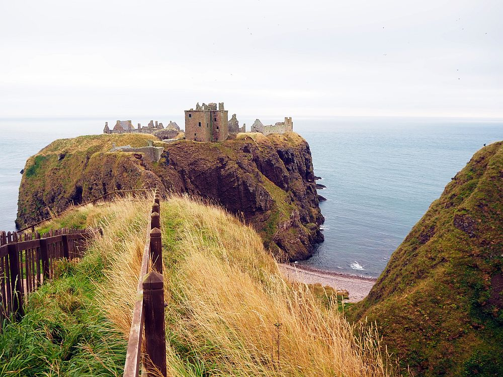 A view of Dunnottar Castle that shows its dramatic setting on a spur of land extending out into the ocean.