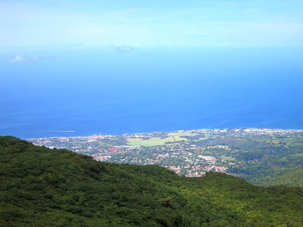 A view from the side of La Soufriere volcano in Guadeloupe shows a very green landscape, a village on the sea, and deep blue water blending into clear blue sky.