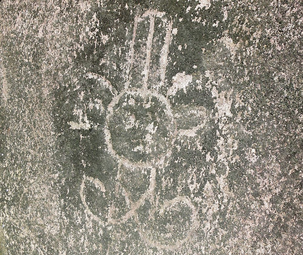 A rock carving left by Arawak people at Carved Rocks Archeological Park shows a very simple figure with a round face, a square body with large feet sticking out the bottom of the body, with no feet and no arms. the round face has what looks like large round ears and a tall hat.
