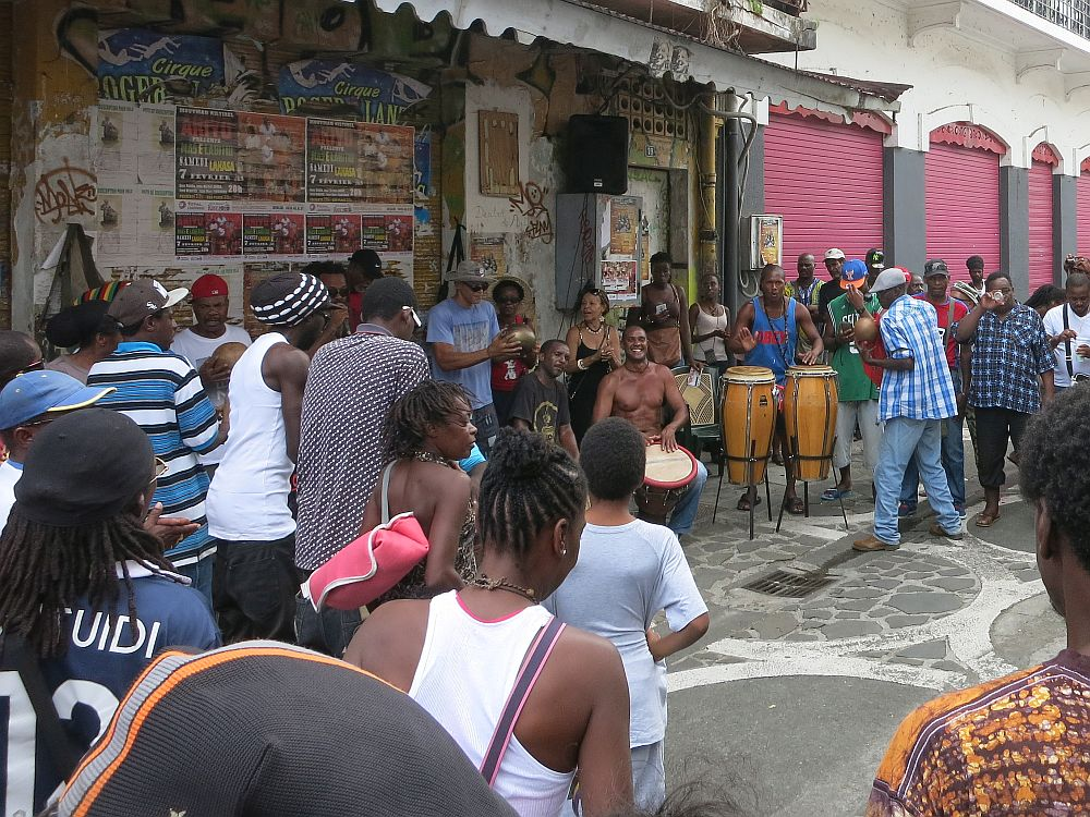 Saturday drumming session in Pointe-à-Pitre: A group of drummers, some sitting with their drums between their knees, some standing with the drums in front of them in stands. A crowd of people stand around them; many have their backs to the camera, and some of the other side of the circle of the audience is visible on the other side of the drums, facing the camera.