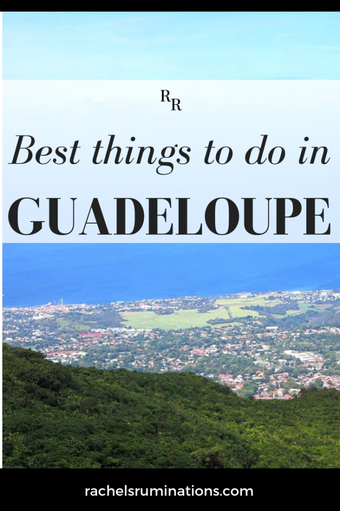 Pinnable image text: best things to do in Guadeloupe image: view from a mountain over a village with the blue sea in the distance