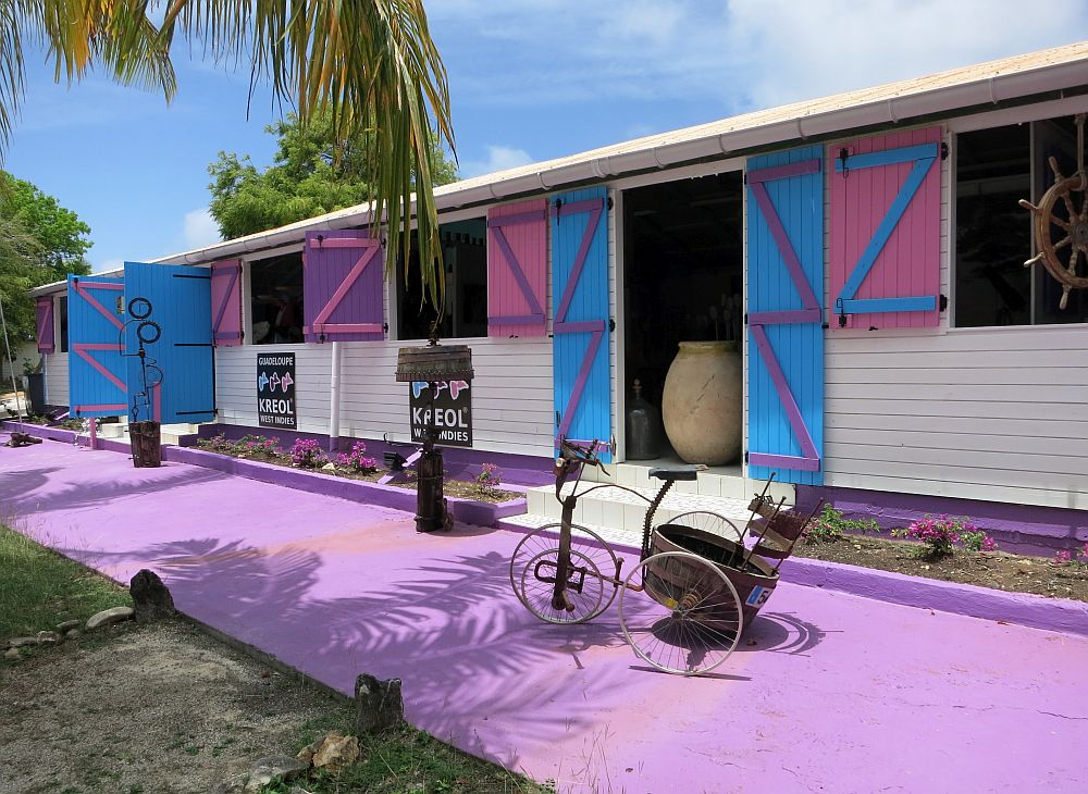 The building is a single story, quite long, with a purple-painted strip of concrete in front and shutters around the open windows (purple) and doors (blue). A few sculptures stand on the concrete strip.
