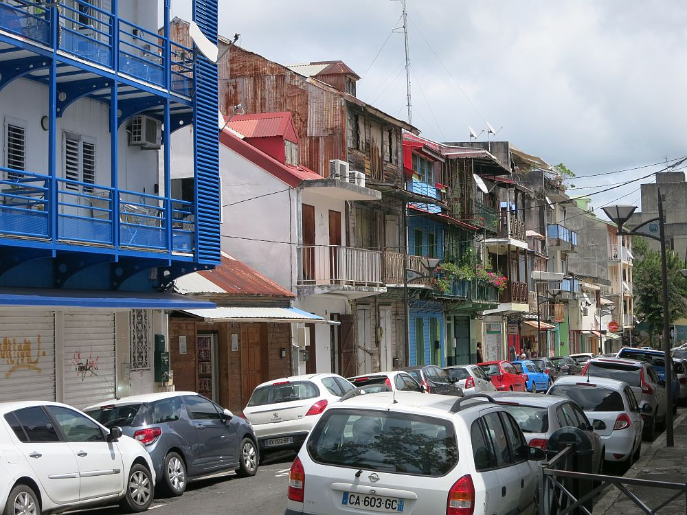 a street scene in Pointe-à-Pitre: a city street with cars parked along both sides. The other side of the street is lined with residential buildings of 3 or 4 stories each. Most have balconies and some are painted in bright colors, while some look very weatherworn.