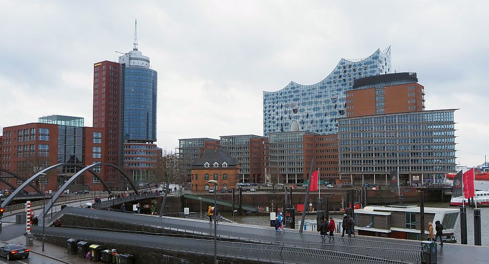 The photo shows a cluster of new buildings, with one small older brick one in the foreground. The Elbphiharmonie in the background has an unusual wavy roofline.