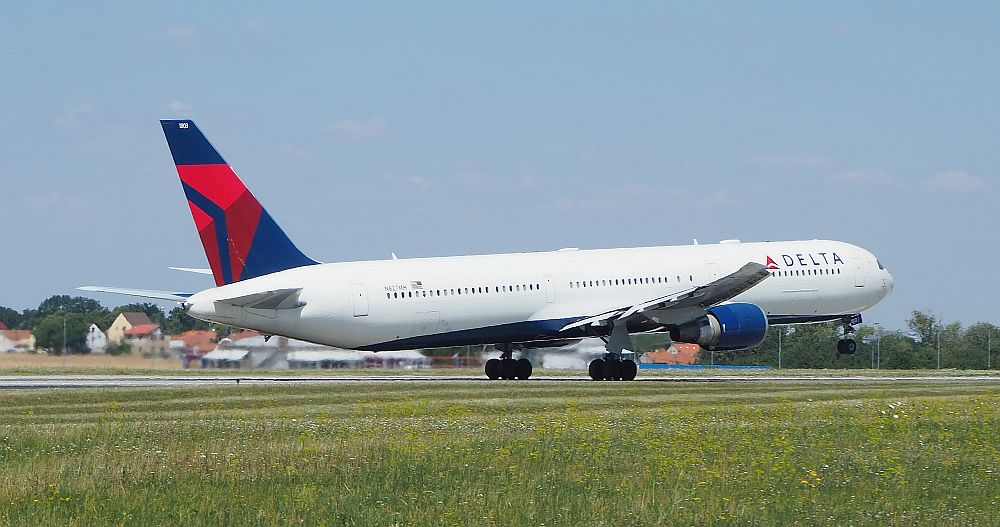 A Delta airlines plane taking off from Prague Airport, it's front wheel just leaving the ground.