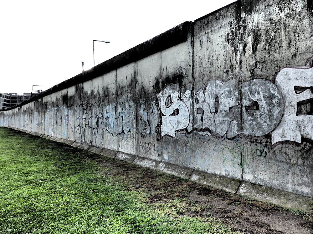 A long piece of the Berlin wall, with some graffiti still visible.