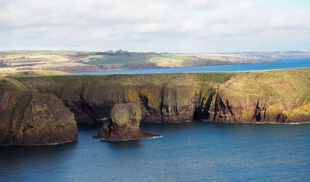 Beautiful views across the water from Dunnottar: flat-topped cliffs and blue water.