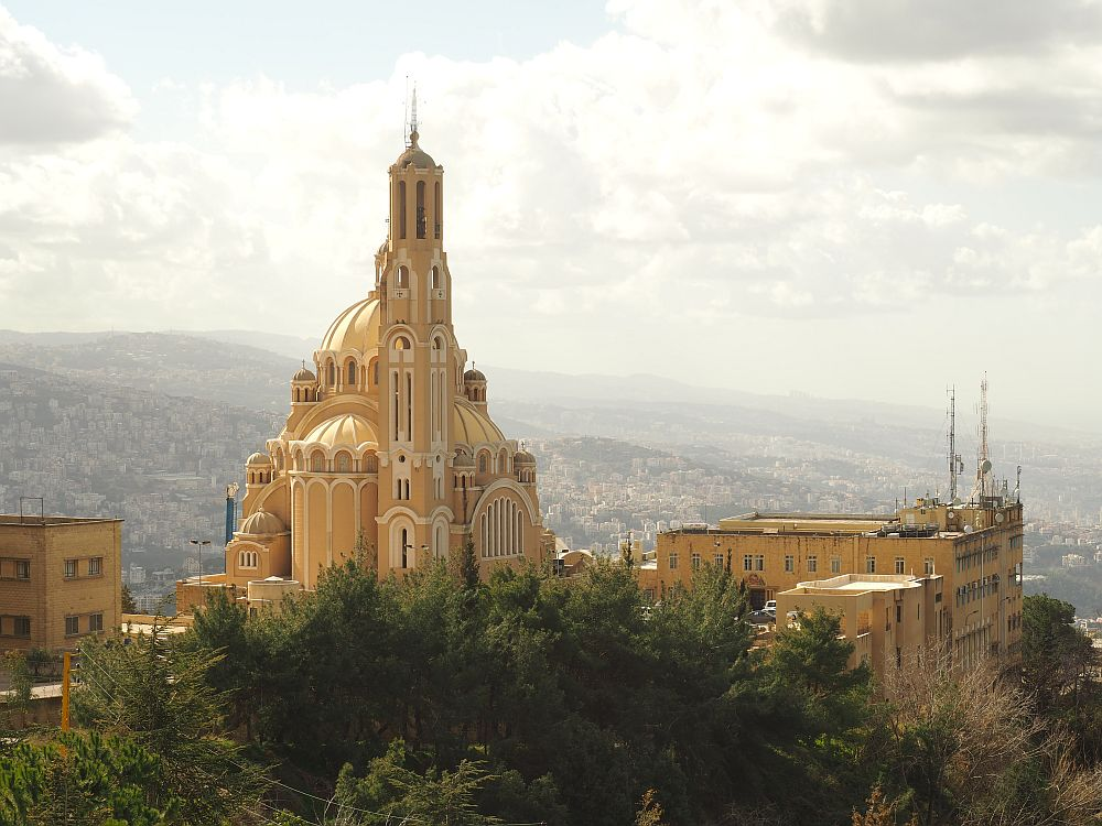 An ornate church in the foreground, a very large city in the hazy distance. Special places in Lebanon: Harissa.