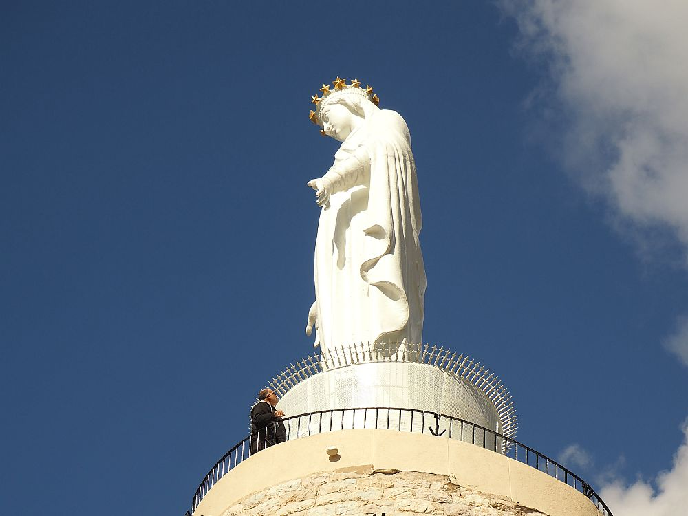 A large white figure of a woman in flowing robes and a golden crown. She has her hands outstretched at her side, palms facing outwards. Special places in Lebanon: Harissa.