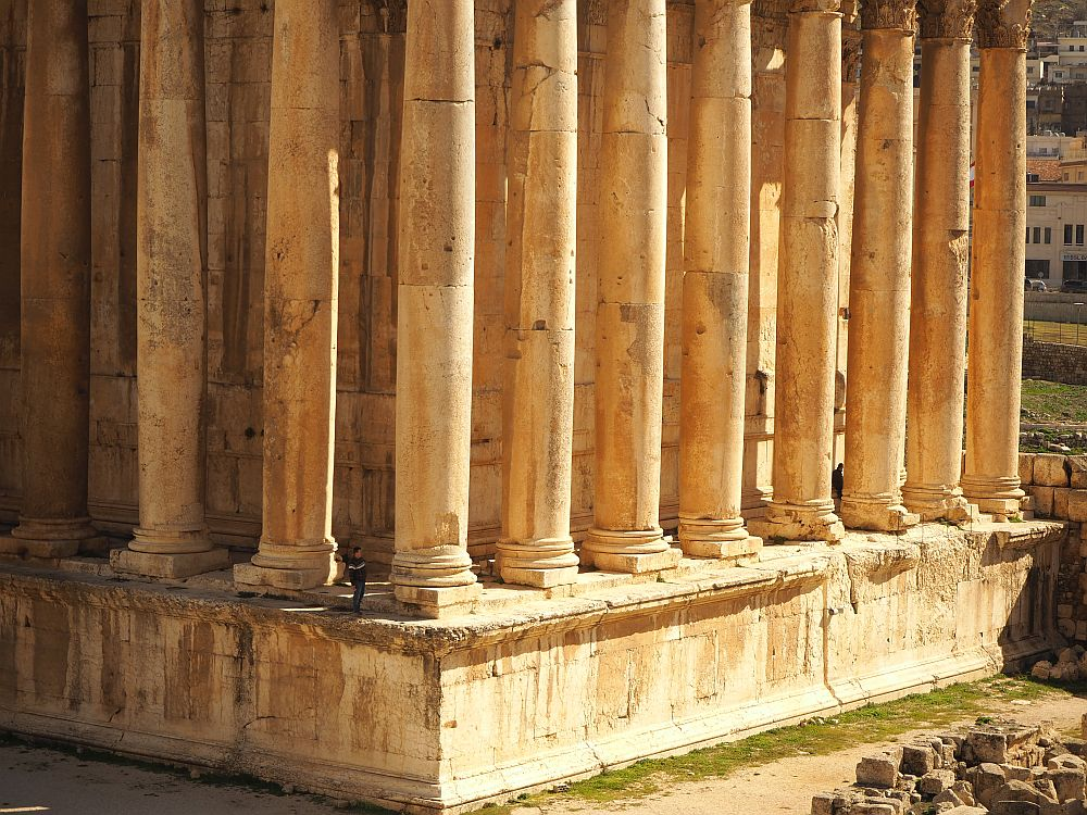 The person is only a bit taller than the plinth that the column stands on. Temple of Bacchus at the Baalbek ruins.