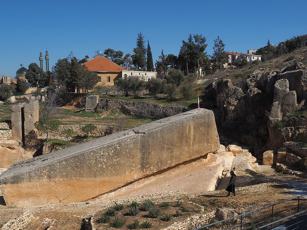 The 1000 ton stone is a long rectangular shape, tilted upward at the uphill end. The woman doesn't even reach the bottom of the stone -- Roman Quarry near Baalbek