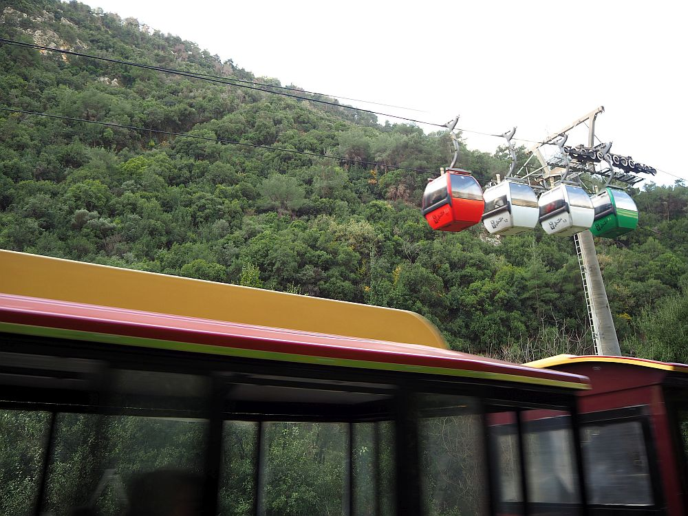 "In the foreground, a blurry roof of the ""train"". In the background, four hanging gondolas on the ropeway cable."