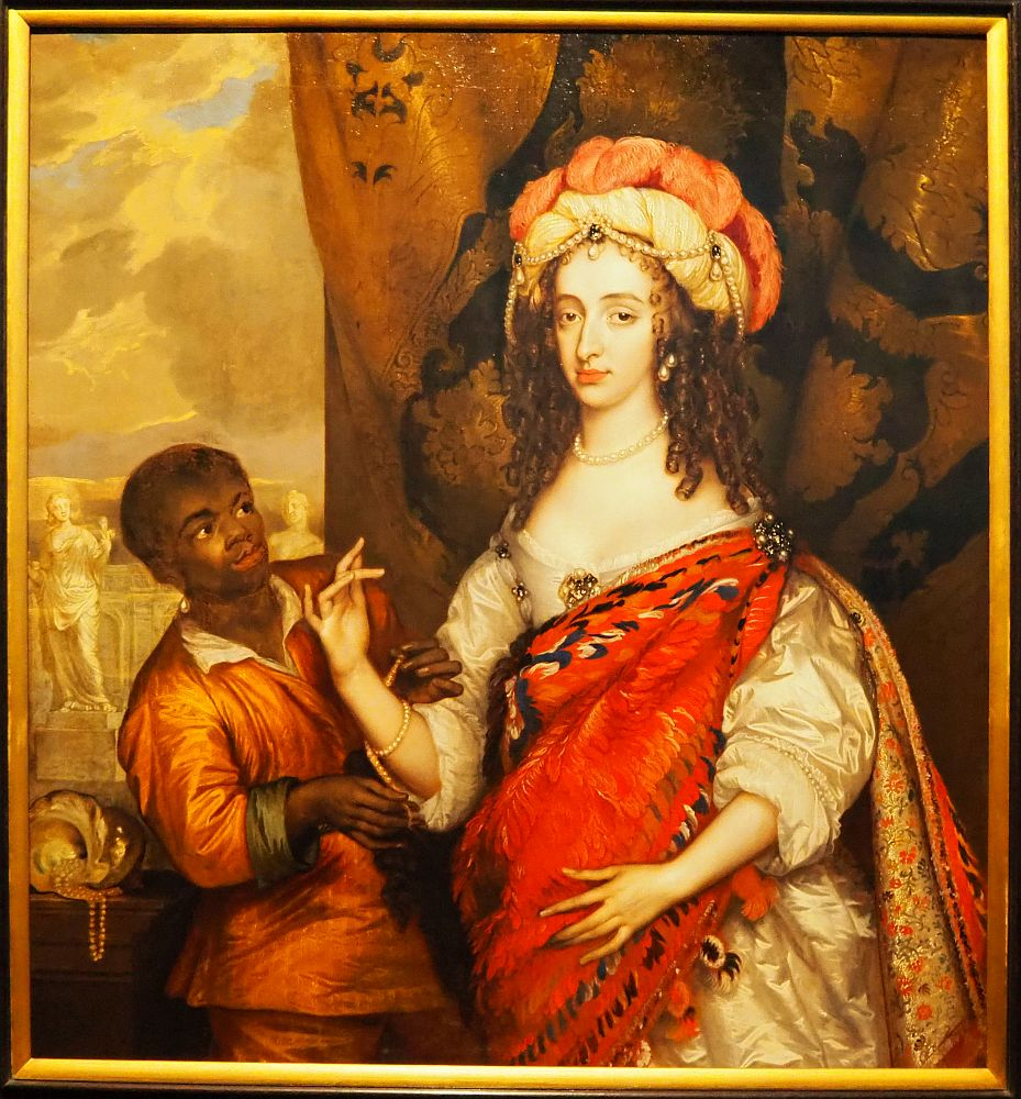 The woman's dress is white, but mostly hidden by the red feathered cloak. The servant boy stands slightly behind her, looking up at her, and helping her put on a bead bracelet.