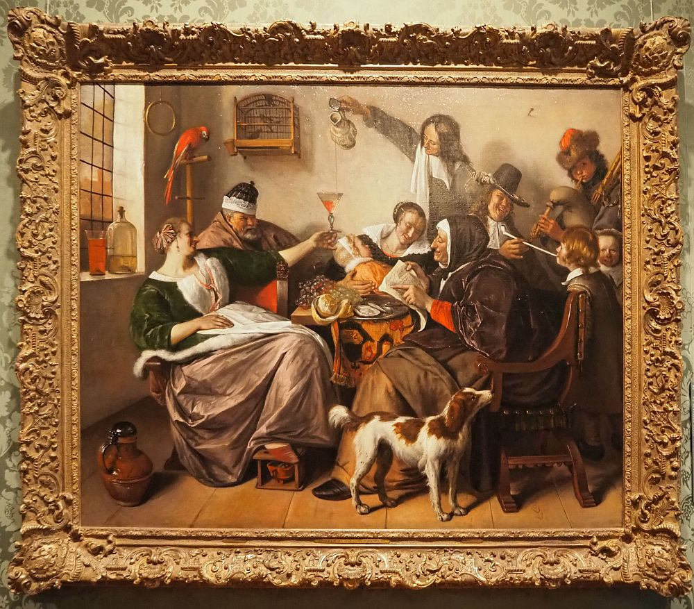 A woman reclines on the left, a pudgy man next to her. A red parrot perches above him. Behind a table, a woman holds a baby and a man reaches over her to pour wine. An old woman reads, a man gives a boy a puff from his pipe, another man plays bagpipes.