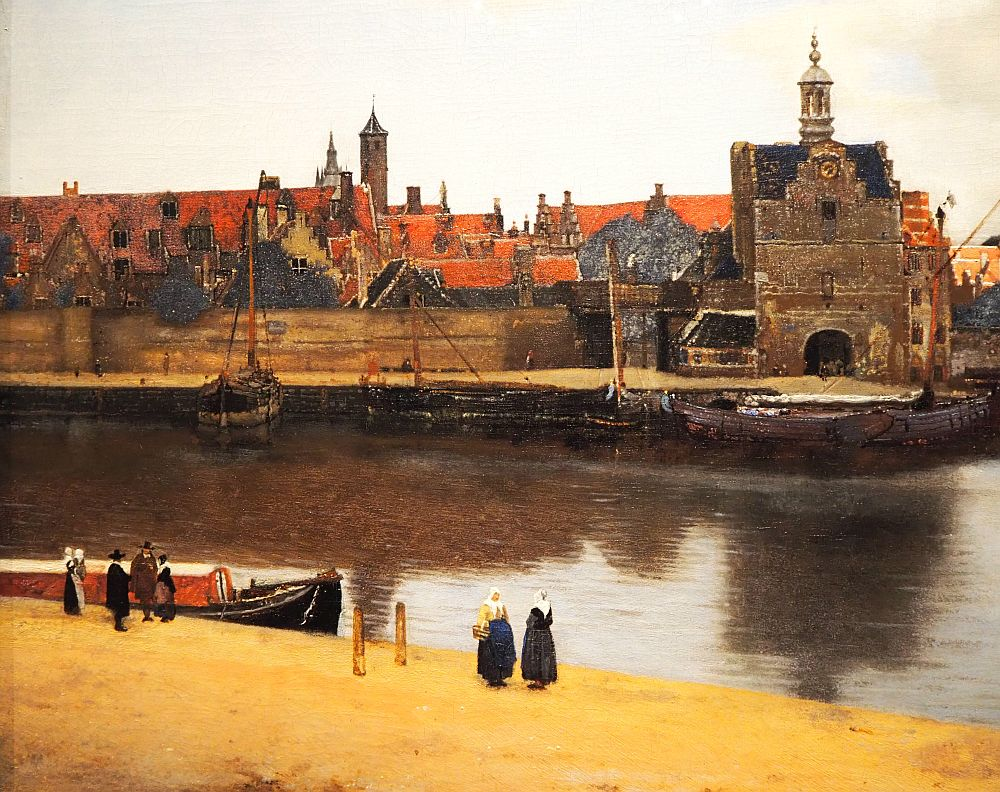 In this detail, a river cuts across the picture horizontally, and the city of Delft is on the far bank. A few people stand on the shore on the near side.