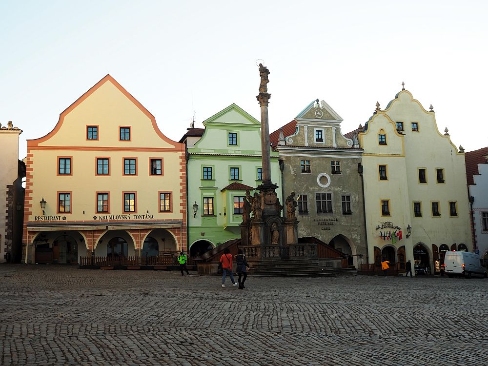 The photo shows four pastel-colored buildings on a cobbled square with a tall carved column in front.