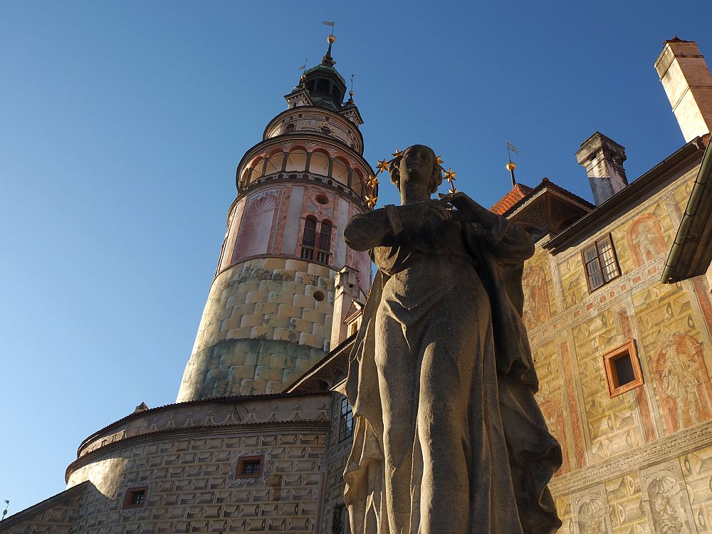 Seen from below a classical statue with a halo looms, with the conical castle tower behind it.