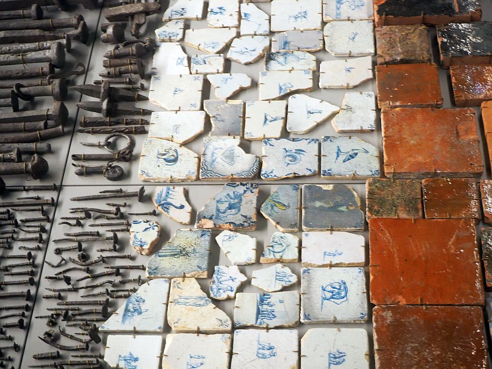 The Delft tiles are white with blue line drawings on each. The floor tiles are clay red.