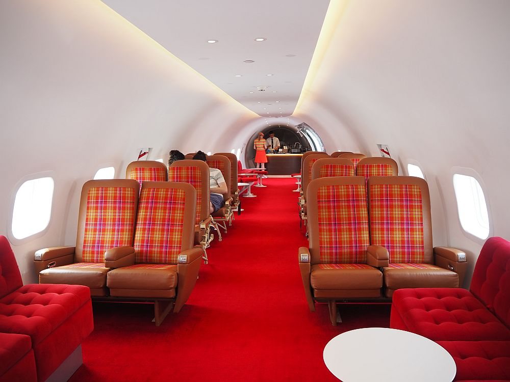 red-carpeted and white-walled, the airplane seats are red and brown leather, much more cushioned and larger than airplane seats nowadays. A bar is visible at the rear of the plane.