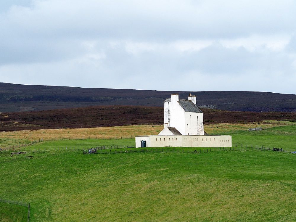 the building is vertical and simple and painted white, with a low, whitewashed wall around it, in the middle of a field.