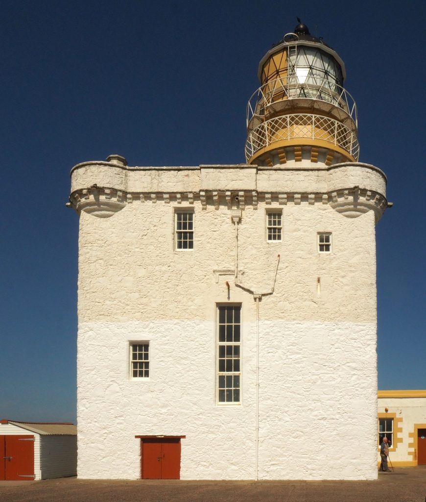 A plain white block of a castle tower, topped with a lighthouse light.