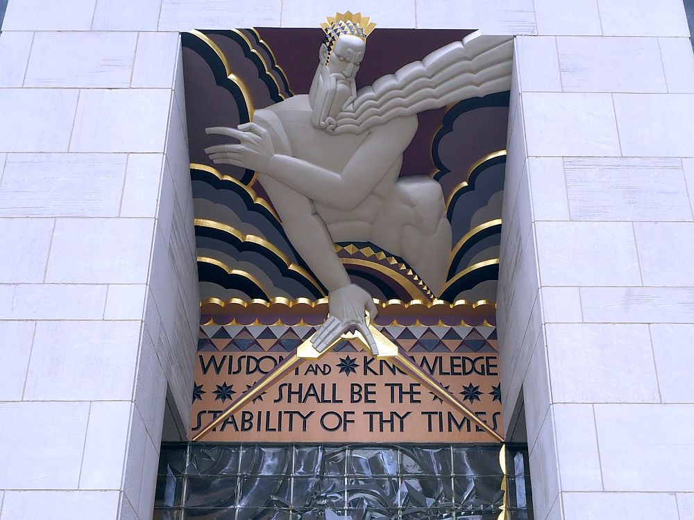 "The figure of a god leans over the entrance. Underneath it is the text ""Wisdom and knowledge shall be the stability of thy times."""