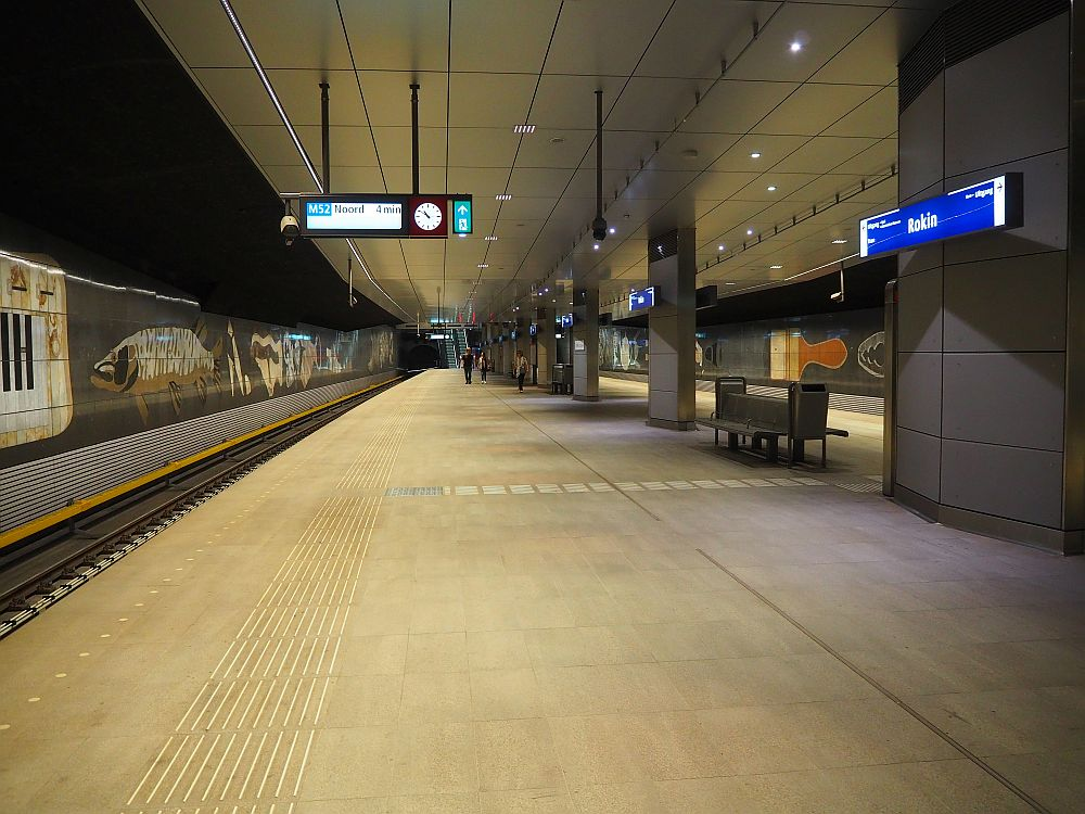 a view down the length of the station: big empty concrete platform with tracks on either side. The walls next to the tracks have large mosaics on them.