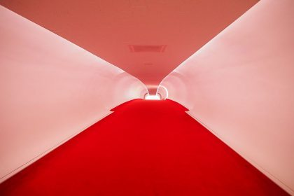 The hallway is long and upward-sloping, with white walls and ceiling and bright red carpeting on the floor.