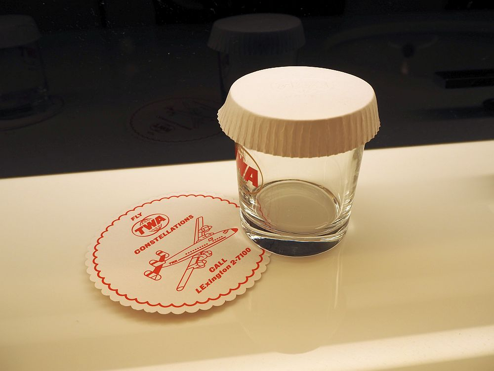 "In the bathroom, a glass with the TWA logo and a coaster that reads ""Fly TWA Constellations. Call LExington 2-7100."