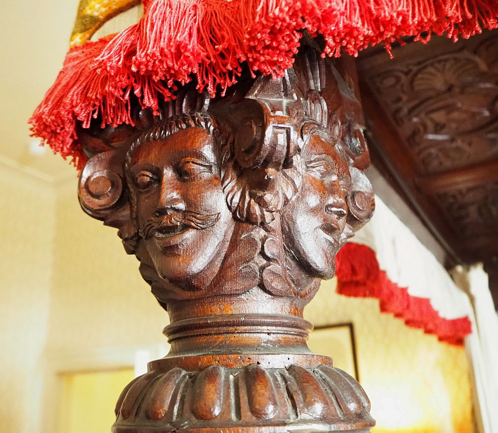 The bedpost is thick and has 4 faces, each on a side, carved in the wood.