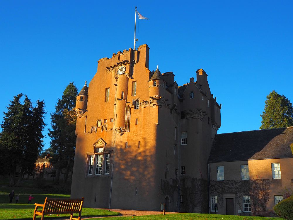 The whole building is visible with its little towers and crenellations. It is tinted orange in the sunlight against a blue sky.