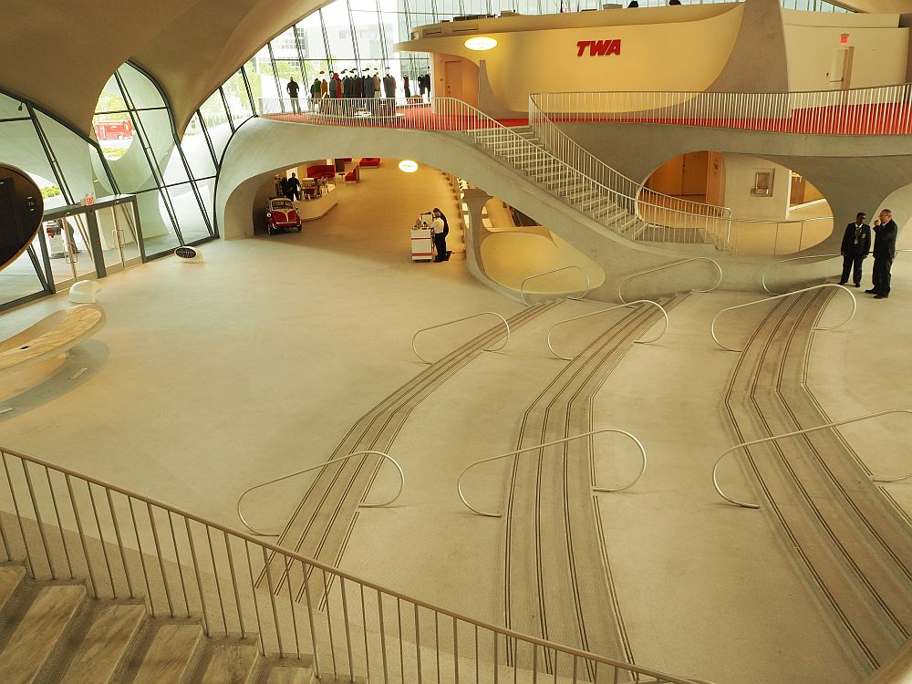 The lobby is very wide and white floored and empty, with shallow stairs leading up from left (the entrance) to the right side of the picture.