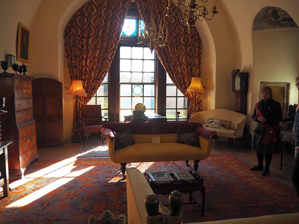 An arched window with draped curtains lets light into a room with a couch, a dark carpet, armchairs, cupboards, etc.