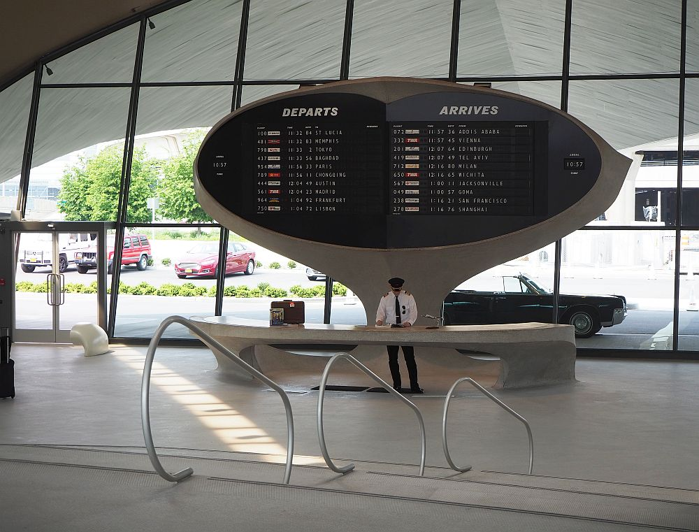 Inside the front entrance of the TWA Hotel, an actor dressed as a pilot poses underneath the departures board. A vintage car is parked outside.