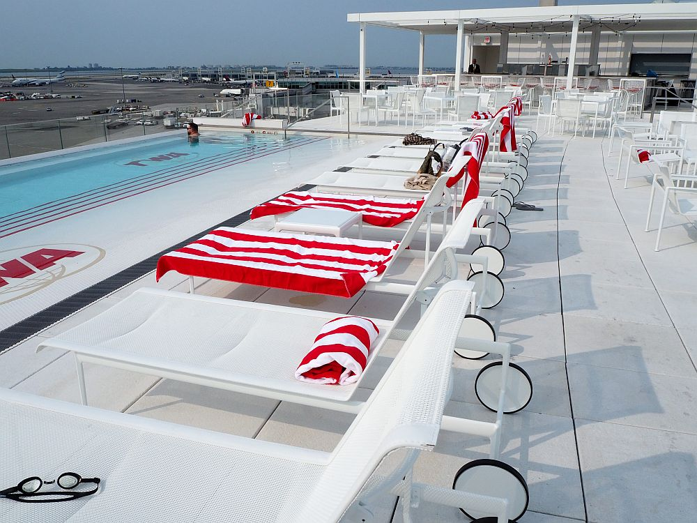 A row of white lounge chairs fill the center of the photo, some draped with bright red and white towels. On the left, a portion of the pool is visible, quite narrow, with a bit of the runway visible behind it.