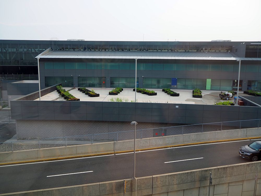 The side of Terminal 5 is visible, with a road passing in front of it. It seems have some sort of garden boxes under a glass roof.