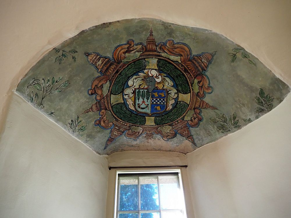 The painting that remains shows a coat of arms on the small ceiling above the window, which is set in a thick wall at Crathes Castle in Scotland