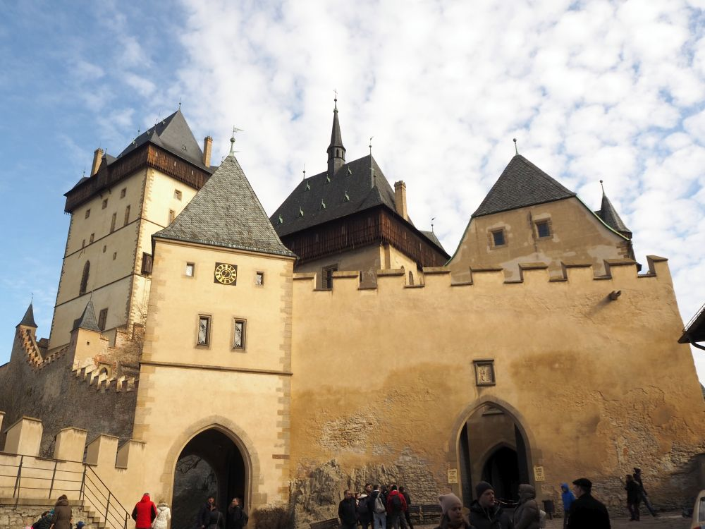 A large wall with crenellations and a gateway, and three towertops visible behind it.