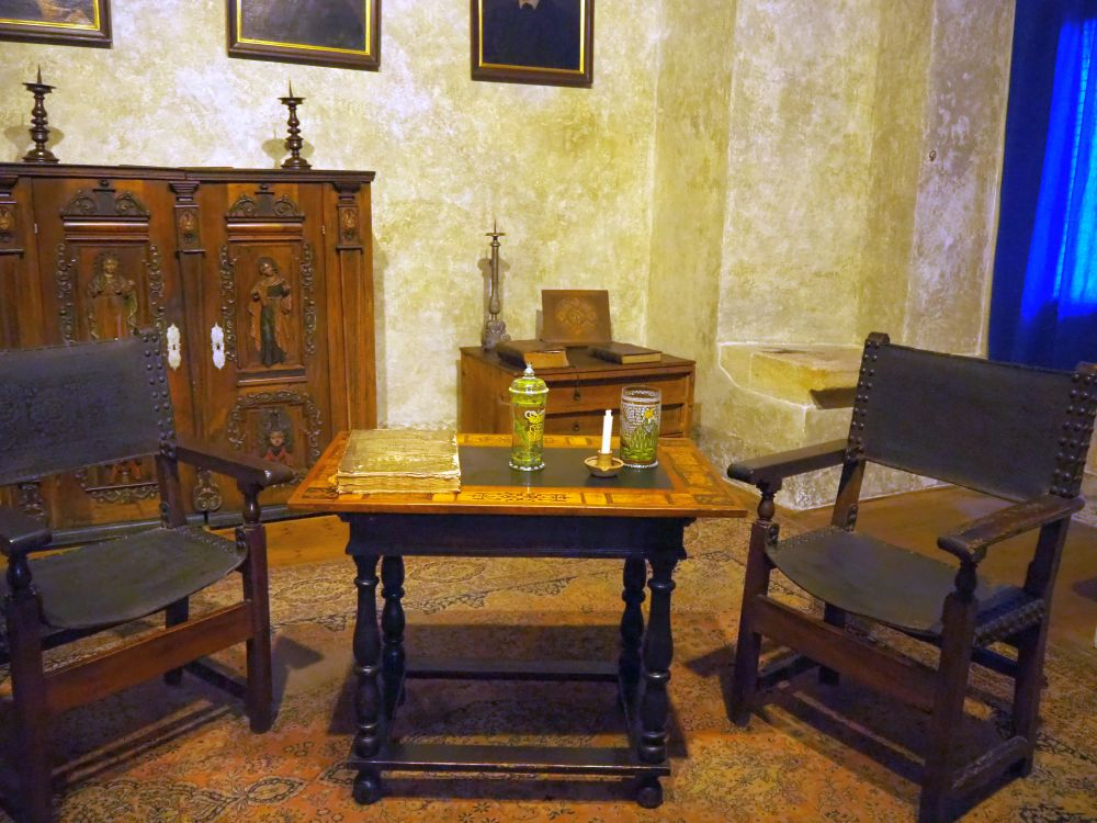 Two simple chairs frame an inlaid table, with a cabinet in the background and paintings on the wall behind.