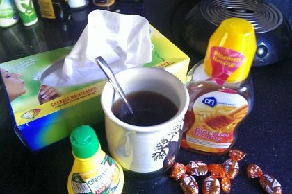 a box of kleenex, a cup of tea with lemon juice and honey, and cough drops