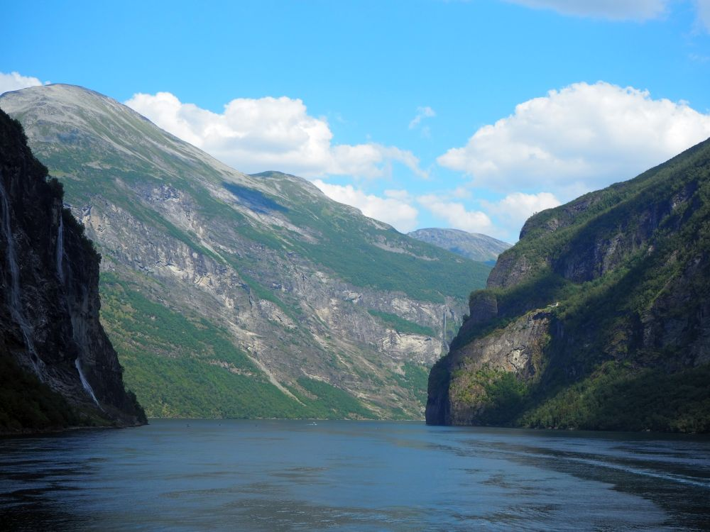 A view into the fjord: dark water ahead, a steep cliff on either side and a larger mountain straight ahead with a mix of rock and green ground cover.
