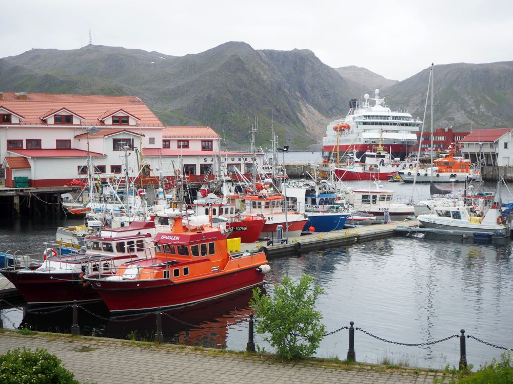 A cluster of small fishing boats moored on a dock, with the Hurtigruten ship visible in the background, and rocky, bare mountains visible beyond that.