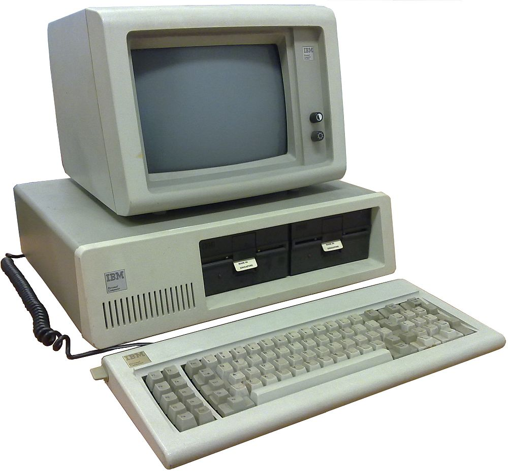 An early IBM personal computer, beige, with a fat monitor sitting on the computer itself, which has two slots for floppy disks. A keyboard sits in front, not much different from keyboards today.